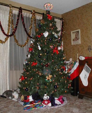 Західний стиль: ялинка великих розмірів, під ялинкою знаходяться новорічні подарунки, а біля неї- Панчішки для членів родини