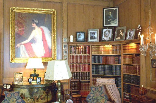 В кабинете сочетаются разные осветительные приборы: люстра из хрусталя, торшер и светильник в цвете желтой меди и декоративными абажурами