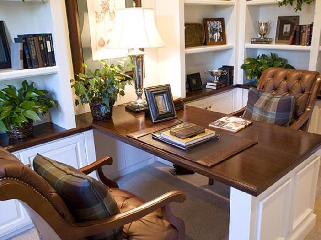 Качественные кожаные кресла в кабинете, обращают на себя внимание подушки с клетчатым узором из натуральной ткани