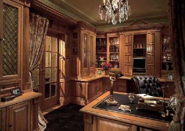 Кабинет исполнен в приглушенных, слегка тусклых тонах, используется декоративная лепнина и шторы из тяжелых тканей, техника спрятана за фасадами роскошной мебели из дерева в классическом стиле
