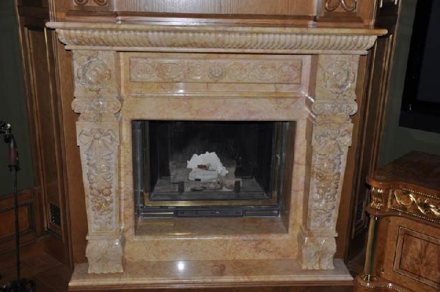 Камин, отделанный мрамором с декоративным узором, в классическом стиле