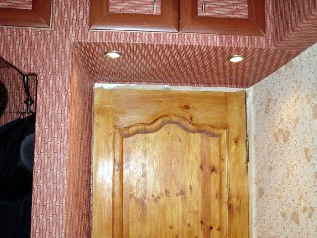 Одна стена возле двери оклеена светлыми обоями, а остальные — темными. Короткая прихожая кажется длиннее и шире