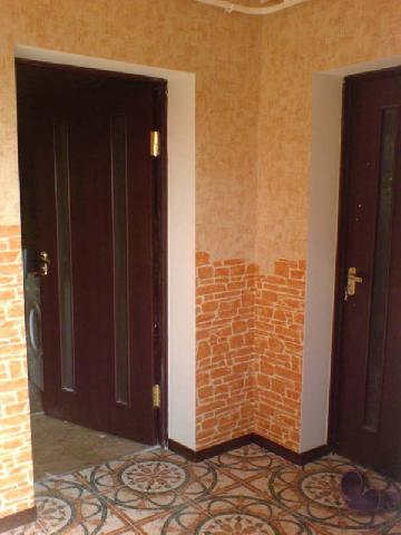 В прихожей обои имитируют кирпичную кладку на стенах