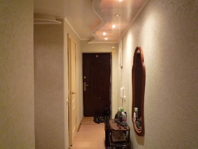 Обогащает интерьер прихожей коридора криволинейная конструкция из гипсокартона на потолке