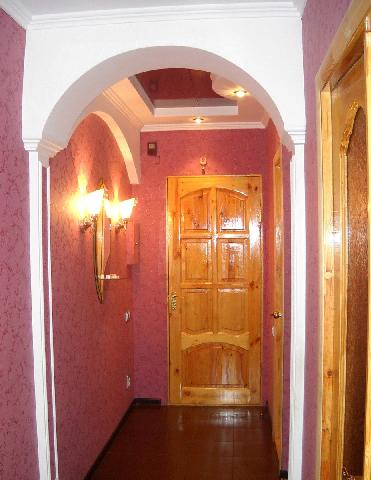 Направленные вверх светильники возле зеркала «поднимают» потолок в коридоре