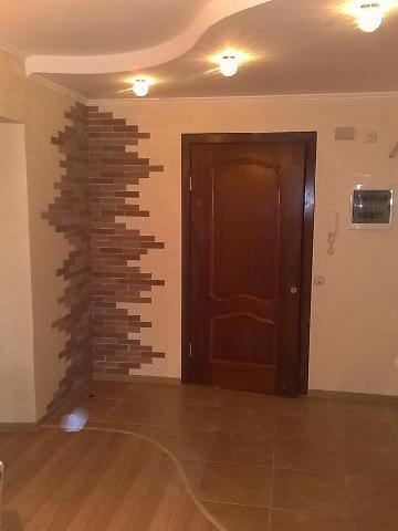 Небольшая прихожая отделена с помощью напольного покрытия, контуры которого повторяют очертания потолка