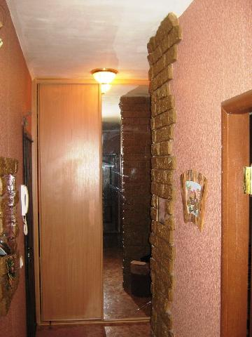 В прихожей стены отделаны обоями и кладкой из камня, что не скрадывает пространство благодаря ее визуальному увеличению с помощью глянцевого натяжного потолка