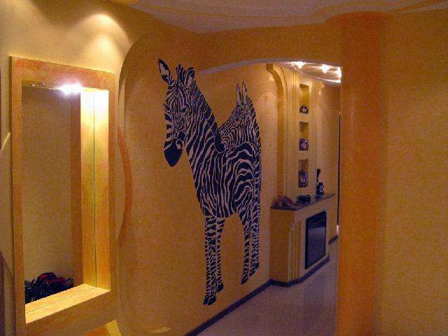 Желтый цвет в интерьере прихожей делает ее уютной и теплой, а рисунок зебр вносит некий колорит