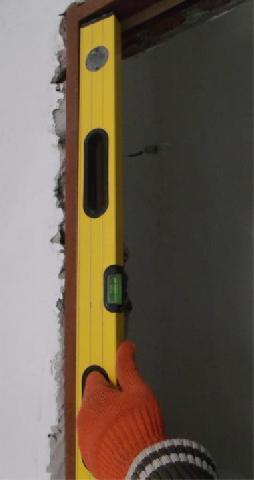 Проверка правильности положения дверной коробки уровнем