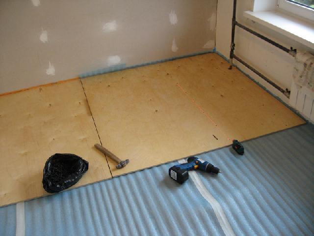 Процесс крепления фанерного листа к бетонному основанию с помощью дюбелей или шурупов