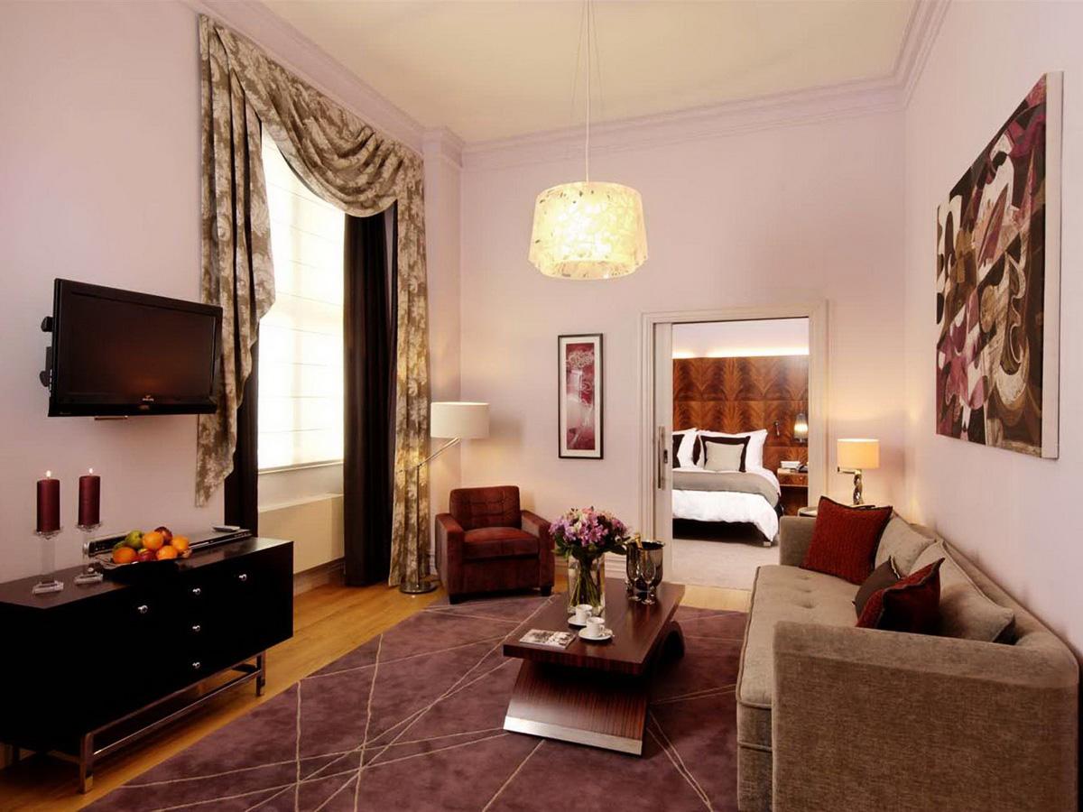 Слишком высокую гостиную можно визуально сделать ниже с помощью бордюра под потолком
