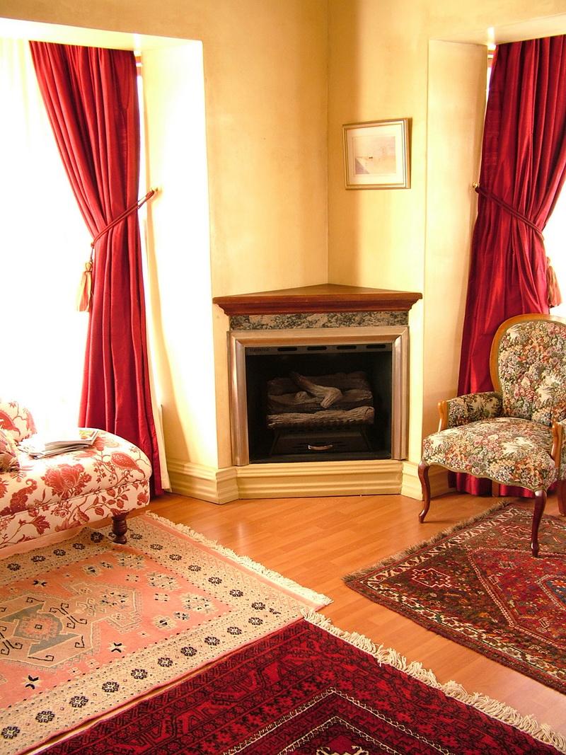 Шторы на подвязках с кисточками – характерная черта классического стиля, но несколько ковровых покрытий немного портят интерьер