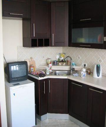 Для небольшой кухни в классическом стиле подойдут темные мебель, но без лишнего декора